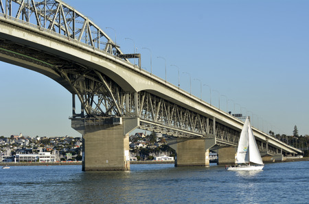 allowing: AUCKLAND,NZ - MAY 28 2014:Yacht sail under Auckland Harbor Bridge.It is 1,020 m (3,348 ft) long, with a main span of 243.8 m, rising 43.27 m above Waitemata Harbour allowing ships access. Editorial
