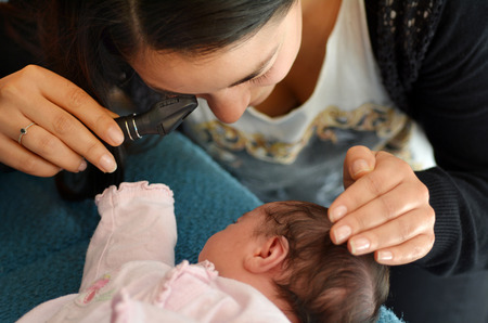 AUCKLAND - JUNE 14 2014:Midwife checks newborn baby red reflex examination.The test detect conditions that distort or suppress the normal visual image and can lead to blindness in children. Publikacyjne