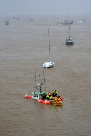 lashing: MANGONUI, NZL - JULY 10 2014:Rescue team try to save a sinking boat.High winds lashing the upper North Island of New Zealand have knocked sank boats, blown roofs off houses and cut power to thousands. Editorial