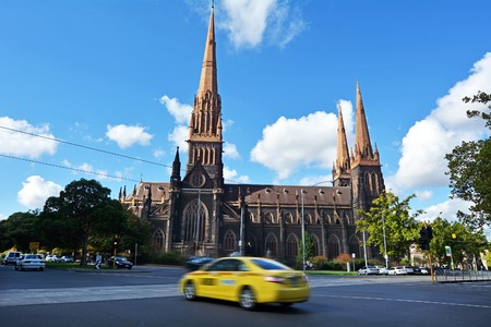 taxicab: MELBOURNE, AUS - APR 14 2014: Taxicab under St Patricks Cathedral, the tallest and, overall, the largest church building in Australia.