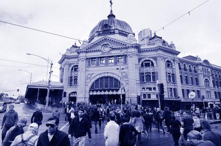 crossings: MELBOURNE, AUS - APR 11 2014:Pedestrians cross Flinders Street towards Flinders Street railway station.Its on of the most busiest pedestrian crossings in Australia and the busiest of Melbournes.