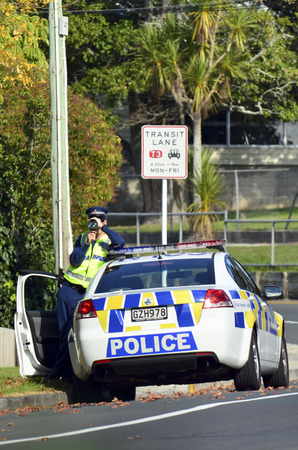 'pull over': AUCKLAND,NZ - JUNE 03 2014:Traffic Police officer pointing his radar gun at speeding traffic.Traffic Police Monitor traffic to ensure motorists observe traffic regulations and exhibit safe driving procedures.
