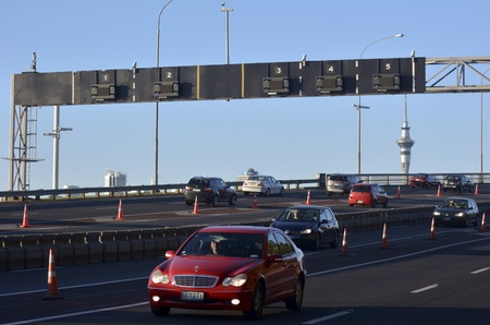presently: AUCKLAND,NZ - MAY 27 2014:Traffic on Auckland Harbor Bridge in Auckland, New Zealand.The daily average number of cars crossing the Auckland Harbour Bridge is presently around 165,000