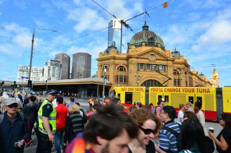 crossings: MELBOURNE, AUS - APR 13 2014:Pedestrians cross Flinders Street towards Flinders Street railway station.Its on of the most busiest pedestrian crossings in Australia and the busiest of Melbournes.