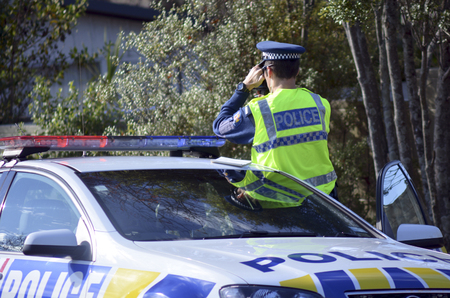 safe driving: AUCKLAND,NZ - JUNE 03 2014:Traffic Police officer pointing his radar gun at speeding traffic.Traffic Police Monitor traffic to ensure motorists observe traffic regulations and exhibit safe driving procedures.
