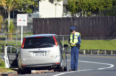 'pull over': AUCKLAND,NZ - JUNE 03 2014:Traffic Police officer writing a traffic citation. Traffic Police Monitor traffic to ensure motorists observe traffic regulations and exhibit safe driving procedures.