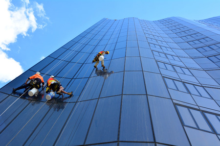 construction work: MELBOURNE - APR 14, 2014:Window cleaners works on high rise building.Window cleaning is considered one of the most dangerous job in the world.Several window cleaners die each year and many are injured