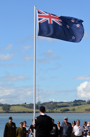national military cemetery: MANGONUI, NEW ZEALAND - APRIL 25 2014: Young New Zealander man is lowering the flag of New Zealand during the National War Memorial day.
