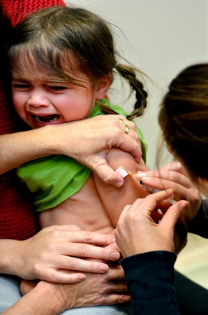 age 5: TAIPA, NZL - MAY 16 2014:A child (Talya Ben Ari age 4) receives an immunization of DPT and MMR vaccine New vaccines could avert nearly 4 million deaths of children under the age 5 by 2015.