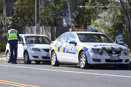 traffic controller: AUCKLAND,NZ - JUNE 03 2014:Traffic Police officer writing a traffic citation. Traffic Police Monitor traffic to ensure motorists observe traffic regulations and exhibit safe driving procedures.