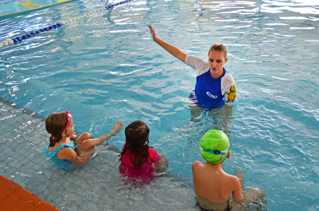 GOLD COAST - OCT 15 2014:Swimming trainer during swimming pool lesson.65% of people in the U.S. don't know how to swim. Editorial
