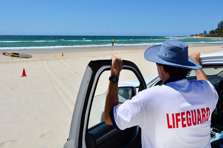 observant: COOLANGATTA - OCT 07 2014: Australian Lifeguards in Gold Coast Australia.Australian Lifeguards are world-renown for their high levels of skill and knowledge in accident prevention and rescue response Editorial