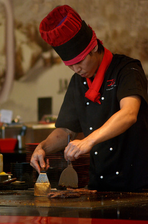 cook griddle: SURFERS PARADISE, AUS - NOV 10 2014:A teppanyaki chef cooking at a gas powered teppan in a Japanese steakhouse.is a style of Japanese cuisine that uses an iron griddle to cook food.