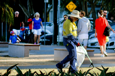 kilograms: SURFERS PARADISE, AUS - NOV 01 2014:Road Sweeper Janitor cleaning street with pointed steel pin tool.Australia is 2nd highest producer of waste in the world at approximately 650 kilograms per person