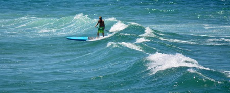 surfers paradise: SURFERS PARADISE - NOV 09 2014:Man on stand up paddling in Surfers Paradise.It one of Australias iconic coastal tourist destinations, drawing about 10 million tourists every year from all over the world.
