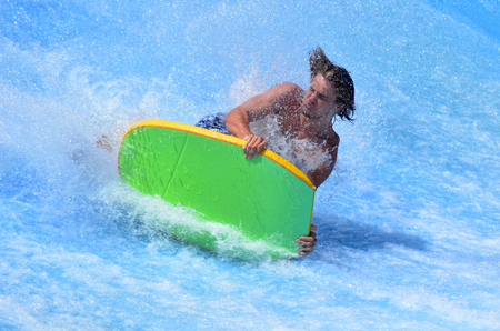 simulate: GOLD COAST OCT 29 2014: Man falling from a surfing board on FlowRider. It is a water park attraction that simulate the riding of waves in the ocean