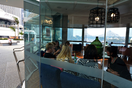 unrivaled: BRISBANE, AUS - SEP 25 2014:Group of women dining in restaurant at Eagle Street Pier.It is an iconic waterfront precinct with world class dining options and unrivaled views of the Brisbane River. Editorial