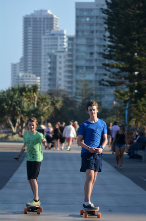 four wheel drive: SURFERS PARADISE, AUS - NOV 01 2014:Young men rid on motorized skateboard over the Esplanade. Its a four wheel drive motorized skateboard capable of reaching 50kmh.