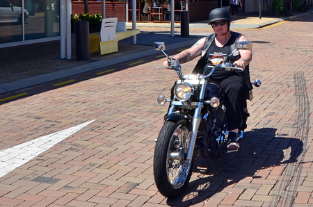 rebelling: GOLD COAST - OCT 19 2014:Man ride Harley-Davidson motorcycle in city street.Harley-Davidson sustains a large brand community which keeps active through clubs, events and a museum. Editorial