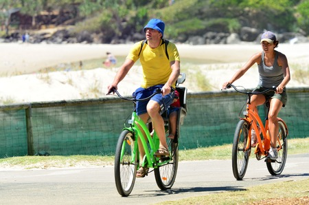 tourist destination: COOLANGATTA - OCT 07 2014:Young couple cycle on Coolangatta waterfront.Coolangatta was one of the earliest settlements on the Gold Coast today its a very popular tourist destination in Australia.