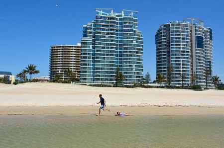 tourist destination: COOLANGATTA - OCT 07 2014:Father and daughter having fun in Coolangatta beach.Coolangatta was one of the earliest settlements on the Gold Coast today its a very popular tourist destination in Australia.