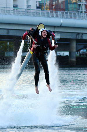 packs: GOLD COAST - OCT 10 2014: Woman ride a Jet pack.The first jet pack was developed in 1919 by the Russian inventor Aleksandr Fyodorovich Andreyev. Editorial