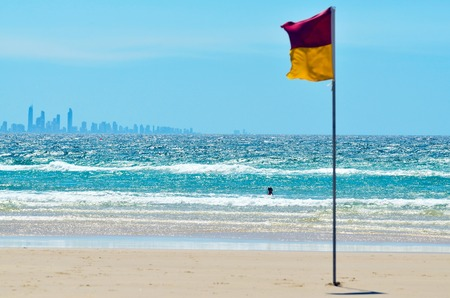 first australians: COOLANGATTA - OCT 07 2014:Australian person swim at sea beside a Lifeguards flag.According to Australia National Drowning report 300 people drown in 2012 with cost of 1 billion to the Australian economy.