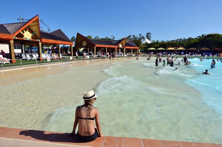 water park: GOLD COAST, AUS - OCT 30 2014:Visitors in Giant Wave Pool at WetnWild Gold Coast water park. In 2009, the park received 1,095,000 visitors ranking it first in Australia and eighth in the world Editorial
