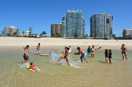 tourist destination: COOLANGATTA - OCT 07 2014:Family having fun in Coolangatta beach.Coolangatta was one of the earliest settlements on the Gold Coast today its a very popular tourist destination in Australia. Editorial
