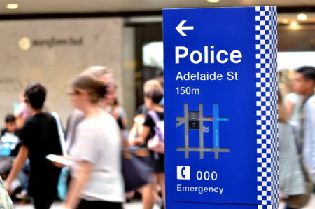 be alert: BRISBANE, AUS - SEP 25 2014:Australian people pass by Police Station sign.Gold Coast police on high terror alert warned to be hyper vigilant and patrol local mosques and critical infrastructure sites