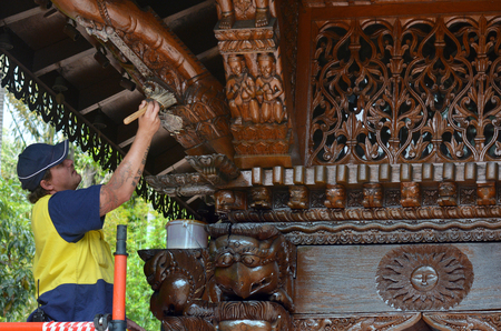the world expo: BRISBANE - SEP 25 2014:Worker varnish a wooden wall of Nepal Peace Pagoda in Brisbane, Australia.It is one of the most significant heritage items in Brisbane from Brisbane World Expo 88 site.