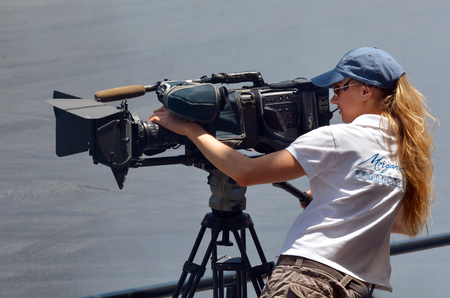 GOLD COAST, AUS - NOV 06 2014:Camerawoman filming. In 2006, there were approximately 27,000 television, video, and motion picture camera operators employed in the United States. Publikacyjne