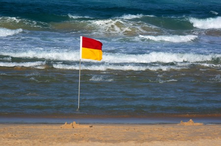 first australians: SURFERS PARADISE - SEP 28 2014:Australian Lifeguards flag.According to Australia National Drowning report 300 people drown in 2012 with cost of $1 billion to the Australian economy.