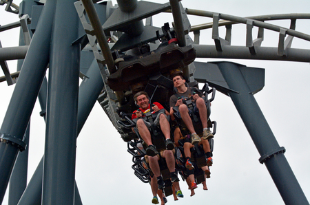 thrill: GOLD COAST, AUS -  NOV 06 2014:Visitors ride on Arkham Asylum – Shock Therapy in Movie World Gold Coast Queensland Australia.It was the first steel inverted roller coaster at an Australian theme park.