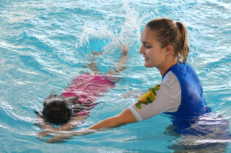 GOLD COAST - OCT 15 2014:Swimming trainer during child (Talya Ben-Ari age 04) swimming pool lesson.Children who have an early swimming experience show improved physical and mental development.