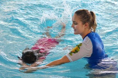 GOLD COAST - 15 oktober 2014: Zwemmen trainer tijdens kind (Talya Ben-Ari leeftijd 04) zwembad lesson.Children die een vroege zwemmen ervaring tonen betere fysieke en mentale ontwikkeling.