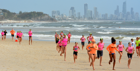 reduce risk: GOLD COAST, AUS - NOV 2 2014:Australian youth runs on the beach.Sport and physical activity for children reduce risk of obesity improve coordination and balance, better sleep and social skills. Editorial