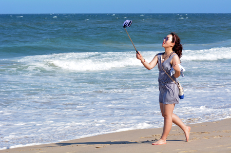 tagged: SURFERS PARADISE, AUS - NOV 01 2014:Asian woman take selfie photo on the beach. Over 1 Million selfies Are taken each day.Instagram has over 53 million photos tagged with the hash tag #selfie.