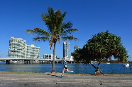 gold coast australia: GOLD COAST, AUS - OCT 13 2014:Man runs under Southport skyline.Its a central business district near the midpoint of the Gold Coast, Australia.