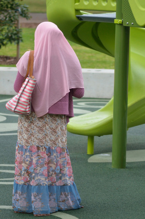 middle eastern families: BRISBANE, AUS - SEP 25 2014:Muslim woman wearing hijab in playground in Brisbane, Australia. According to the 2011 census, 476,291 people, or 2.2% of the total Australian population, were Muslims.