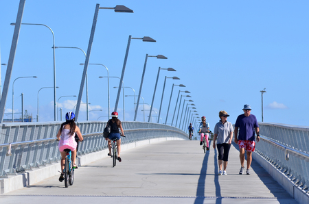 span: GOLD COAST, AUS - OCT 13 2014:People cross over Sundale BridgeThe bridge span across the Nerang River in Southport Gold Coast Queensland Australia.