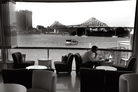unrivaled: BRISBANE, AUS - SEP 25 2014:A businessman dining in restaurant at Eagle Street Pier.It is an iconic waterfront precinct with world class dining options and unrivaled views of the Brisbane River.