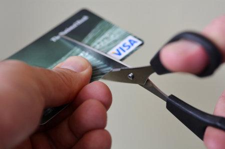 オークランド - 9 月 2014:Man 手クレジット カードをハサミでカットします。深い借金に人々 をことができますので、最低限のクレジット カードの支 報道画像