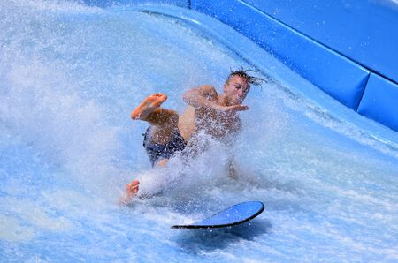 ocean water: GOLD COAST OCT 29 2014: Man falling from a surfing board on FlowRider. It is a water park attraction that simulate the riding of waves in the ocean