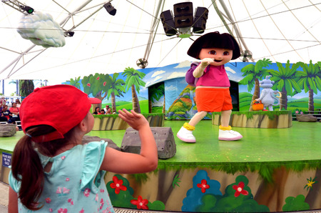 latina america: GOLD COAST, AUS -  NOV 06 2014:Litlle girl (Talya Ben-Ari age 04) with Dora the Explorer.Dora teaches Spanish in the U.S., AUS Canada, NZL and Ireland, but teaches English in the rest of the world.