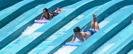 super 8: GOLD COAST, AUS - OCT 30 2014:Visitors rids on Super 8 Aqua Racer in WetnWild Gold Coast water park. In 2009, the park received 1,095,000 visitors ranking it first in Australia and eighth in the world