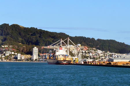 strategically: WELLINGTON - AUG 22 2014:Cargo ship in CentrePort in Wellington NZ.Its New Zealands most strategically situated intermodal hub, road, rail, domestic and international shipping services. Editorial