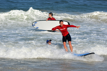 GOLD COAST, AUS - NOV 01 2014:Female wave surfing instructor teaches man and woman how to surf in Surfers Paradise, Queensland, Australia. Editorial