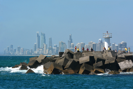 seaway: SURFERS PARADISE, AUS - OCT 28 2014:Visitors on Gold Coast Seaway with Surfers Paradise skyline.Its one of Australias iconic coastal tourist destinations, drawing 10 million tourists a year. Editorial