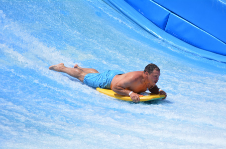 simulate: GOLD COAST OCT 29 2014: Man ride a surfing board on FlowRider. It is a water park attraction that simulate the riding of waves in the ocean